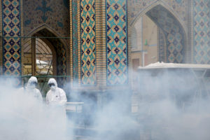 FILE PHOTO: Members of a medical team spray disinfectant to sanitize outdoor place of Imam Reza's holy shrine, following the coronavirus outbreak, in Mashhad, Iran February 27, 2020. Picture taken February 27, 2020. WANA (West Asia News Agency) via Reuters