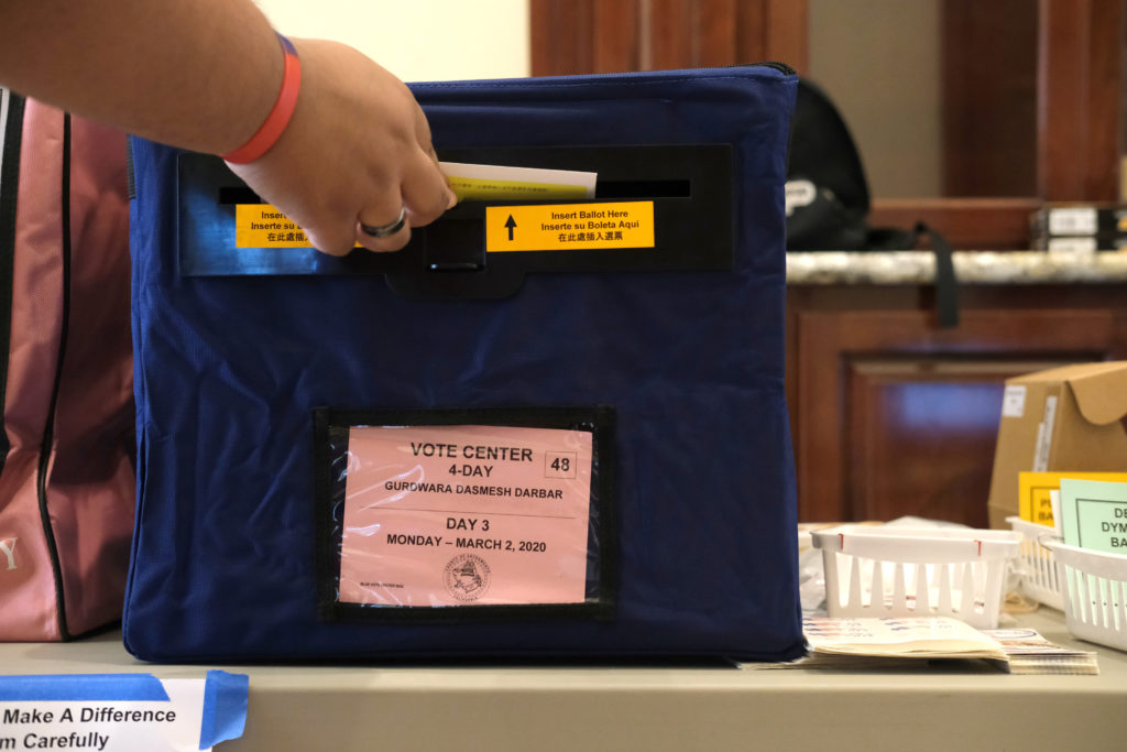 A woman submits her ballot to cast her vote in the California Presidential Primary ahead of Super Tuesday at Gurdwara Dasm...