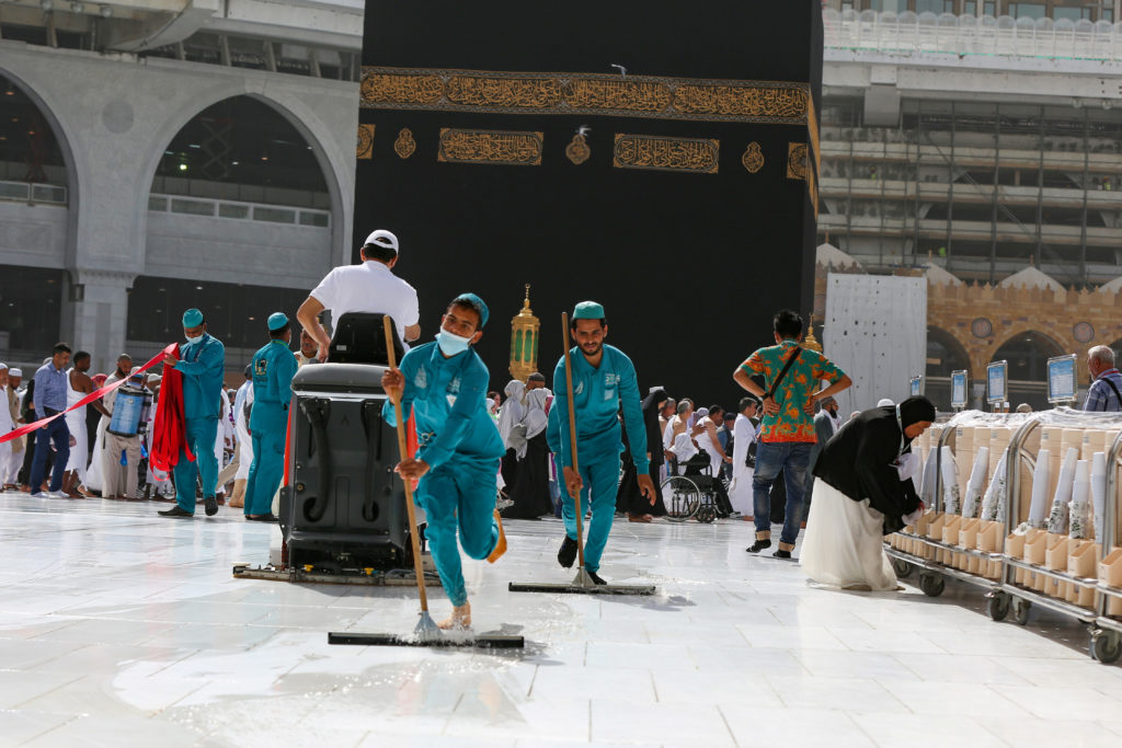Cleaners wear protective face masks, following the outbreak of the coronavirus, as they swipe the floor at the Kaaba in the Grand mosque in the holy city of Mecca, Saudi Arabia. Photo by Ganoo Essa/Reuters