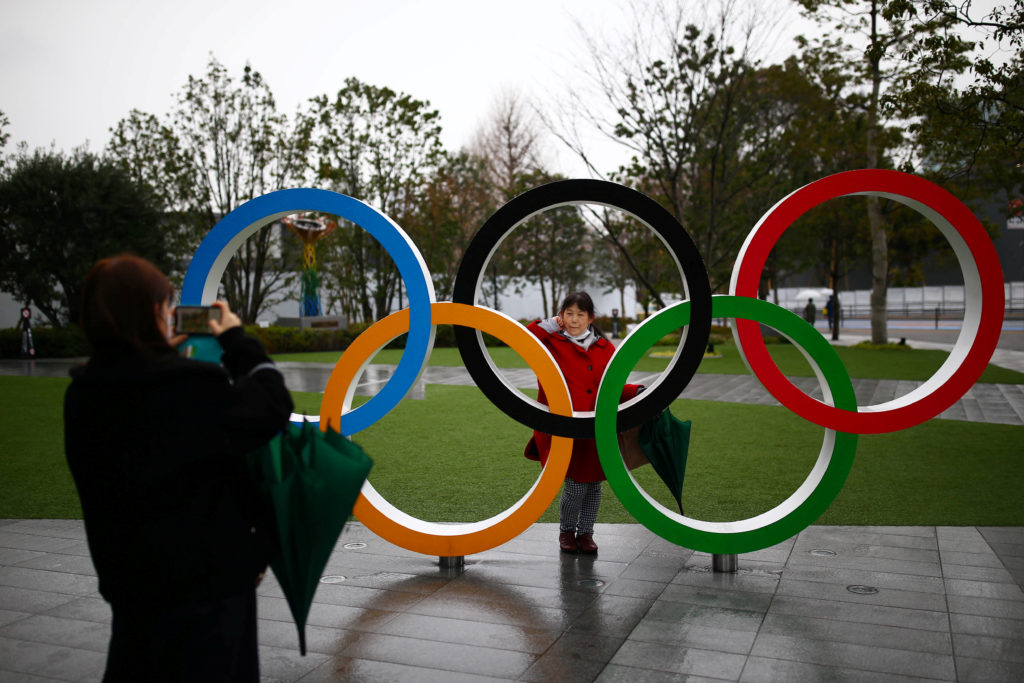 A woman poses for a photo through The Olympic rings in front of the Japan Olympics Museum in Tokyo, Japan. Photo by Edgard Garrido/Reuters