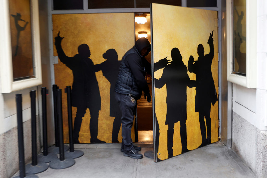 "A worker removes stanchions used for arriving audience members at the Richard Rodgers Theater where the musical ""Hamilton"" plays. Broadway shows have been canceled in the wake of the outbreak. Photo by Mike Segar/Reuters"
