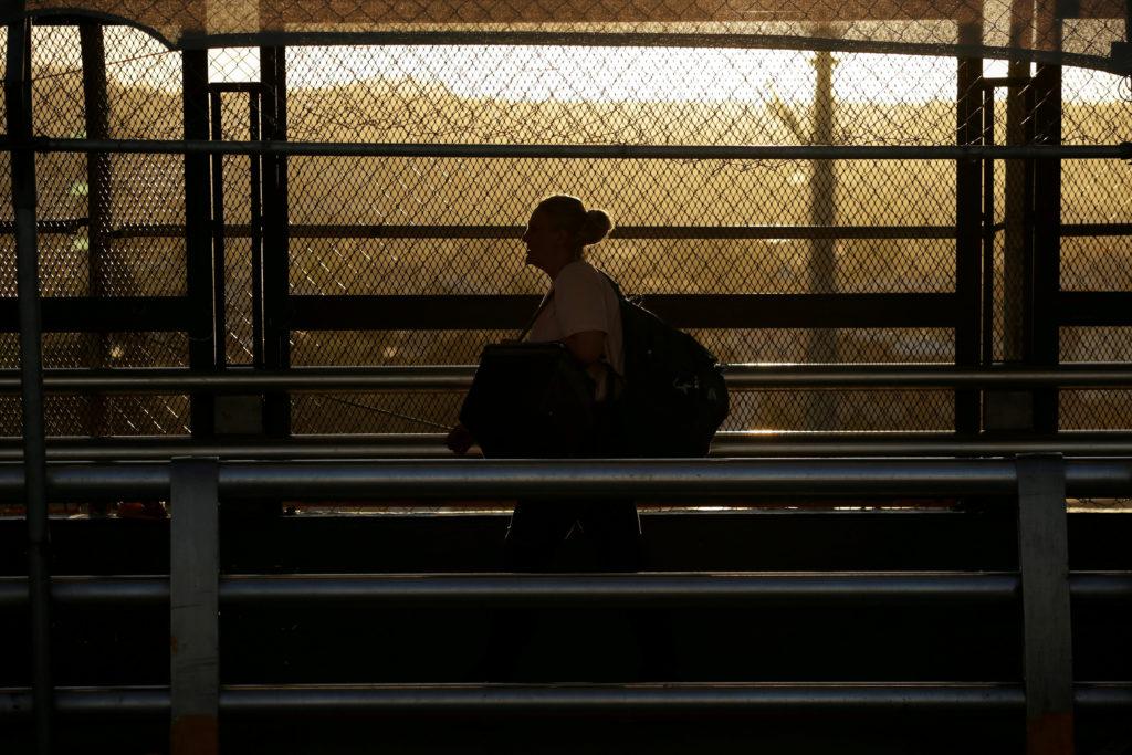 FILE PHOTO: A woman walks towards El Paso, Texas, U.S. at the inter…