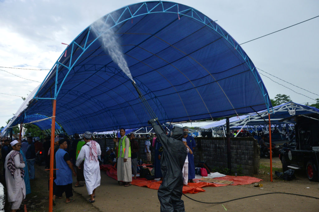 A police officer wearing a protective suit sprays disinfectants on a tent intended for the Muslim pilgrims to stay for mas...