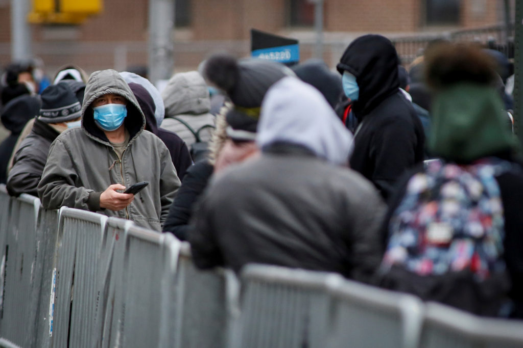 People wait in line to be tested for coronavirus disease (COVID-19) while wearing protective gear, outside Elmhurst Hospital Center in the Queens borough of New York City, March 25, 2020. Photo by Stefan Jeremiah/Reuters