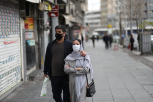 A couple wear protective face masks, amid fear of coronavirus disease (COVID-19), as they walk at Enghelab square, in Tehran, Iran March 26, 2020. Photo by WANA (West Asia News Agency)/Ali Khara via REUTERS