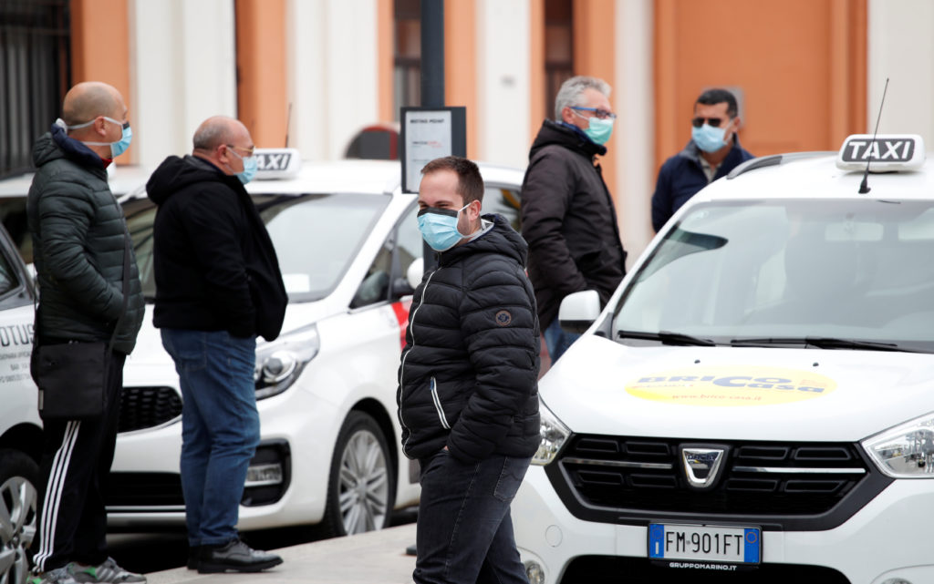 Taxi drivers wearing protective face masks wait for customers outside the Bari Centrale railway station in Bari as the spr...