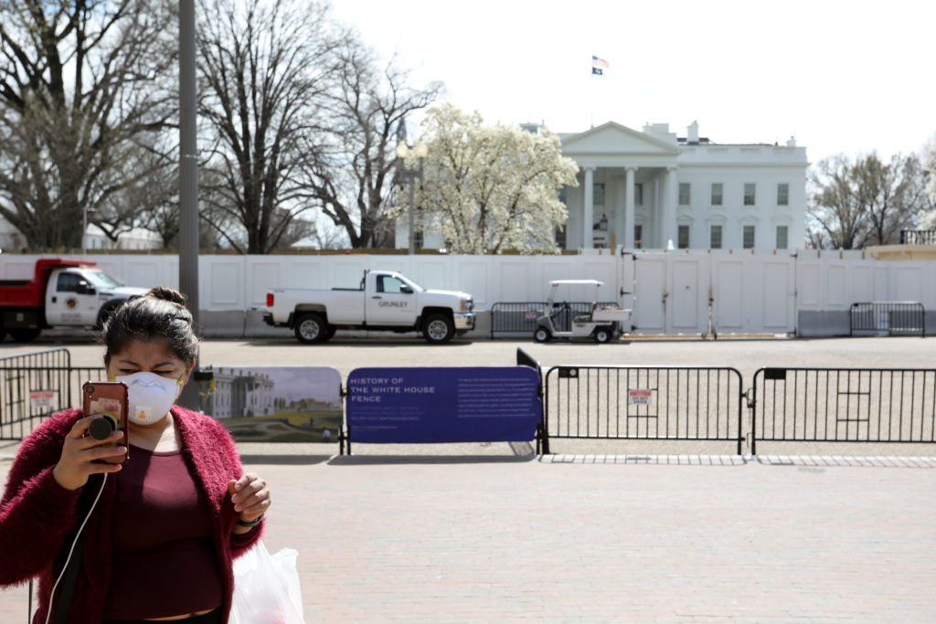 A tourist wearing a face mask takes a picture standing on the pedestrian plaza outside of the White House in Washington, U...