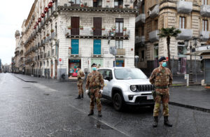 Italian soldiers wearing protective masks work at a roadblock after Italy reinforced the lockdown measures to combat the coronavirus disease (COVID-19) in Catania, Italy March 21, 2020. Photo by Antonio Parrinello/Reuters.