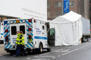 Paramedics walk next to a makeshift morgue set outside Lenox Health Medical Pavilion as the coronavirus disease (COVID-19) outbreak continues in New York, U.S., March 29, 2020. Photo by Eduardo Munoz/Reuters.