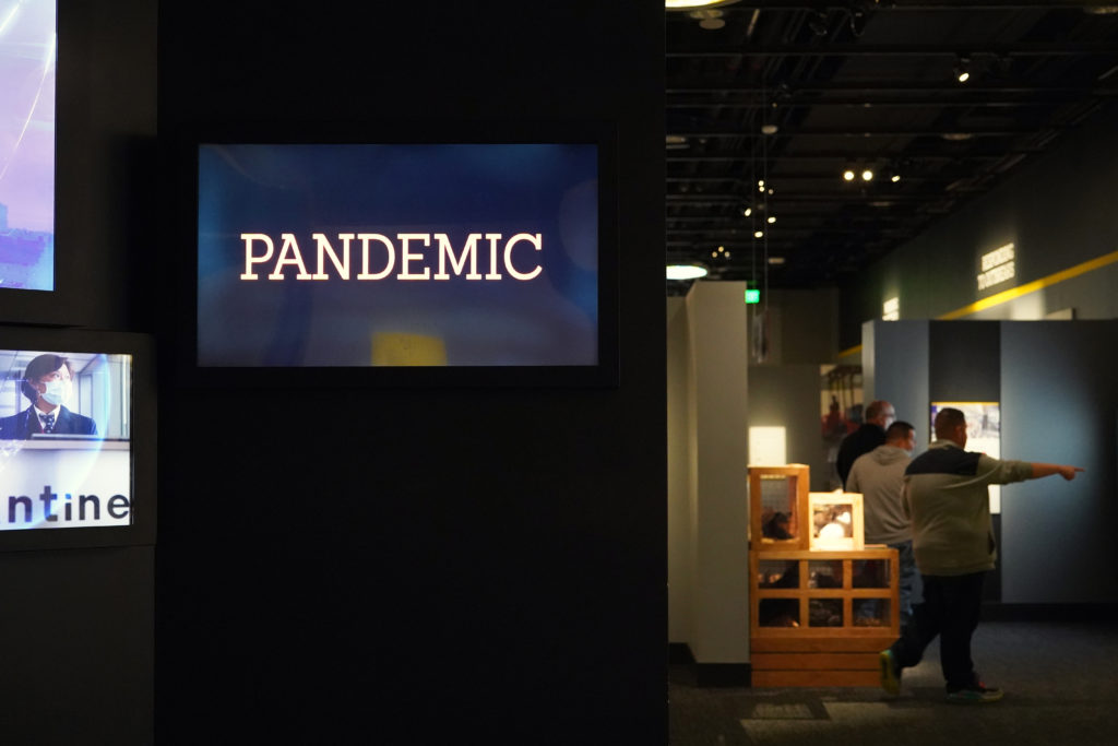 A video at the beginning of the exhibit explains how infectious diseases can emerge and spread across communities, often due to human activities and behaviors. Photo by Joshua Barajas/PBS NewsHour