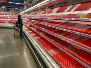 A shopper picks over the few items remaining in the meat section, as people stock up on supplies amid coronavirus fears, at an Austin, Texas, grocery store on March 13, 2020. REUTERS/Brad Brooks