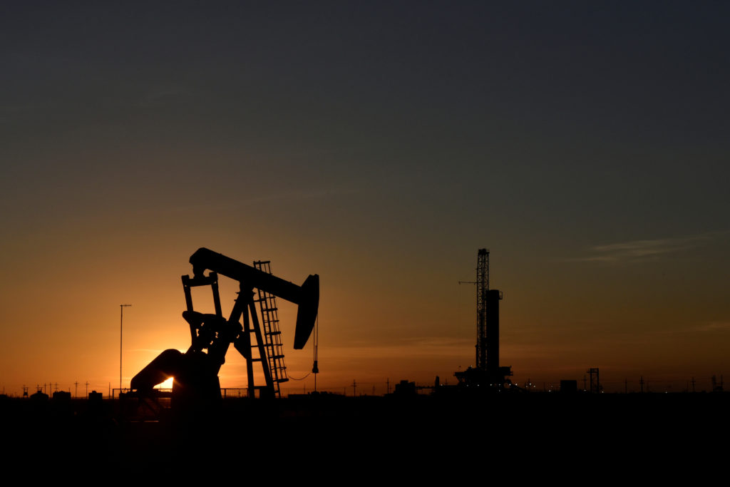 A pump jack operates in front of a drilling rig at sunset in an oil field in Midland, Texas U.S. August 22, 2018. Photo by Nick Oxford/REUTERS