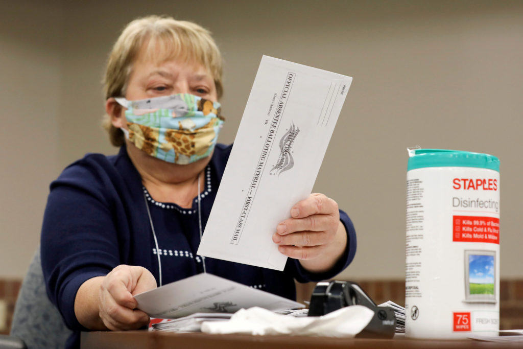 Election volunteer Nancy Gavney verifies voter and witness signatures on absentee ballots as they are counted at the City Hall during the presidential primary election held amid the coronavirus disease (COVID-19) outbreak in Beloit, Wisconsin, U.S. April 7, 2020. REUTERS/Daniel Acker TPX IMAGES OF THE DAY
