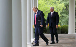 President Donald Trump walks down the West Wing colonnade from the Oval Office with Vice President Mike Pence as they arrive to address the daily coronavirus task force briefing in the Rose Garden at the White House in Washington, on April 14, 2020. Photo by REUTERS/Leah Millis