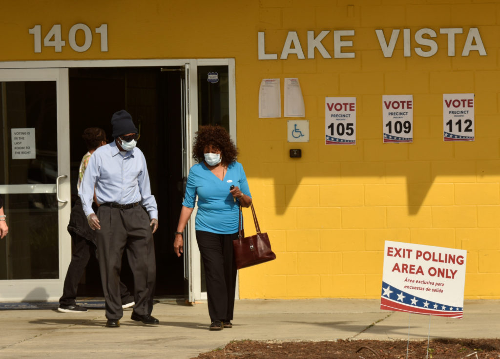 Voters wearing protective masks, due the outbreak of coronavirus disease (COVID-19), walk past election official Brianna Peterson after voting in the municipal and presidential primary elections at their polling center in St. Petersburg, Florida March 17, 2020.  REUTERS/Steve Nesius - RC2XLF9LKISR