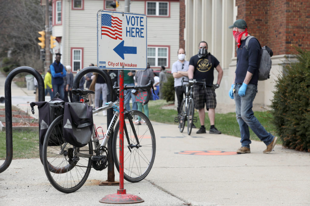 Voters wait in line outside Riverside University High School to cast ballots during the presidential primary election held...