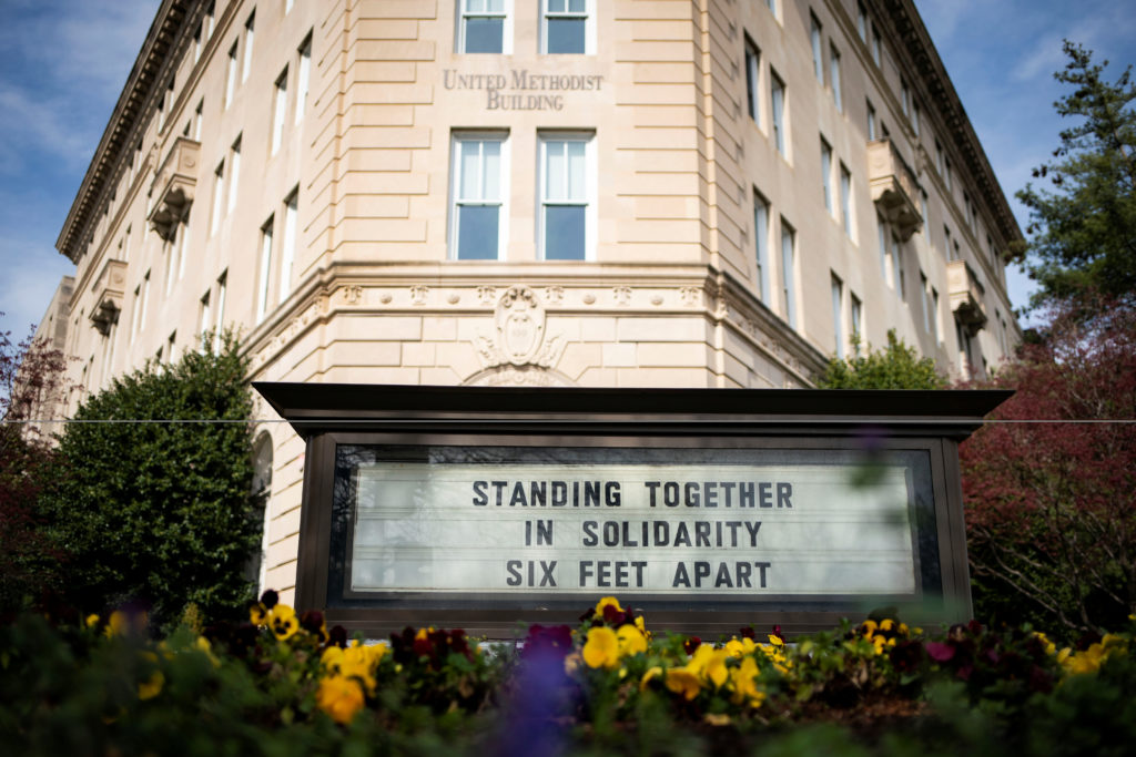 A sign is displayed encouraging social distancing at the United Methodist Building in Washington, U.S., March 24, 2020. Photo by REUTERS/Al Drago