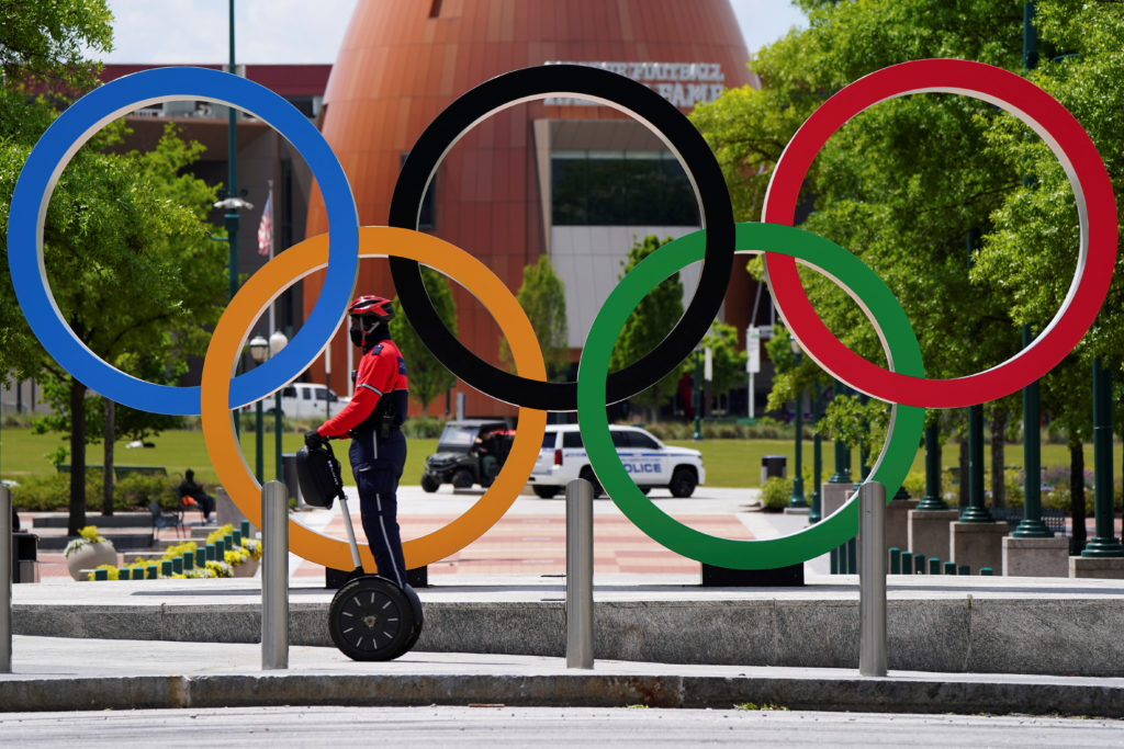 A security patrol on a Segway passes in front of the Olympic rings at Centennial Olympic Park days before the phased reope...
