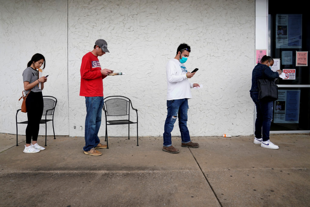 FILE PHOTO: People who lost their jobs wait in line to file for unemployment following an outbreak of the coronavirus disease (COVID-19), at an Arkansas Workforce Center in Fayetteville, Arkansas, U.S. April 6, 2020. Photo by REUTERS/Nick Oxford/File Photo