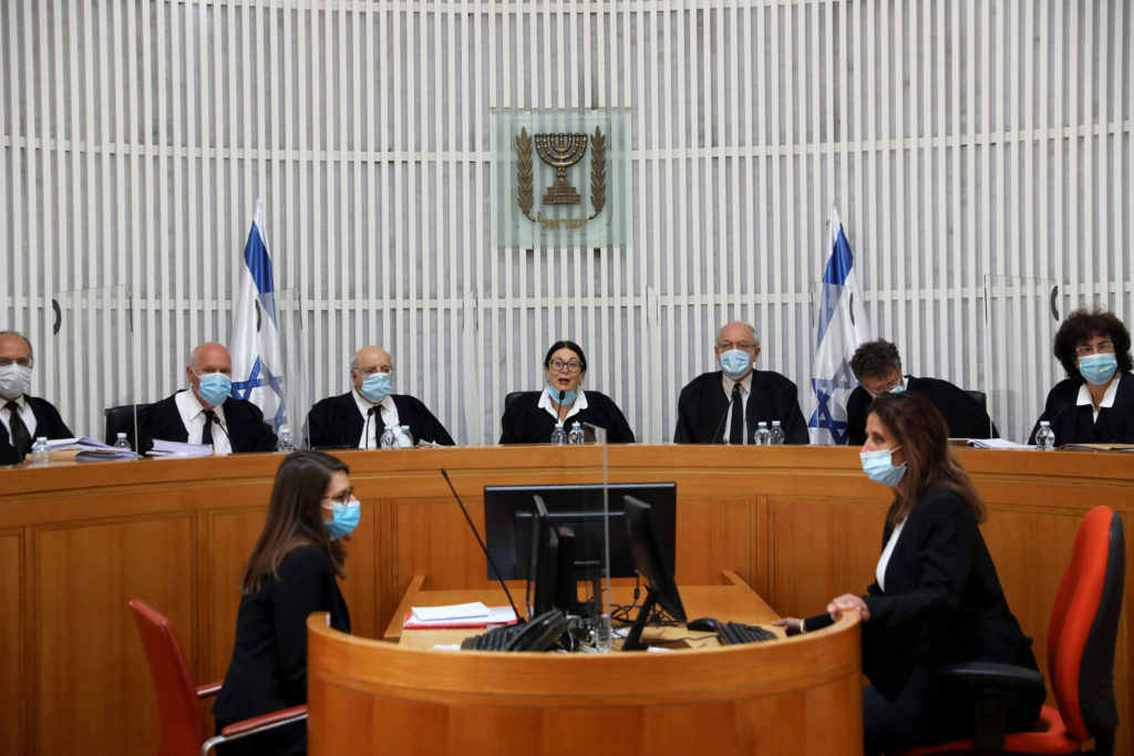 A panel of judges of the Israeli Supreme Court wear face masks as they address a discussion on a petition asking whether I...