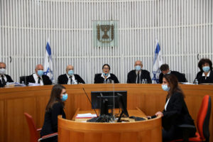 A panel of judges of the Israeli Supreme Court wear face masks as they address a discussion on a petition asking whether Israeli Prime Minister Benjamin Netanyahu can form a government legally and publicly when indictments are filed against him on a charges of fraud, bribery, and breach of trust, at the Israeli Supreme Court in Jerusalem May 4, 2020. Photo by Abir Sultan/Pool via REUTERS