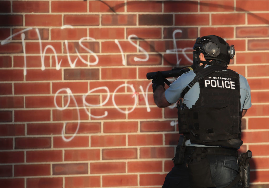 """ST. PAUL, MINNESOTA - MAY 28: Police aim a tear gas gun during a protest on May 28, 2020 in St. Paul, Minnesota. Today marks the third day of ongoing protests after the police killing of George Floyd. Four Minneapolis police officers have been fired after a video taken by a bystander was posted on social media showing Floyd's neck being pinned to the ground by an officer as he repeatedly said, """"I can't breathe"""". Floyd was later pronounced dead while in police custody after being transported to Hennepin County Medical Center. (Photo by Scott Olson/Getty Images)"""