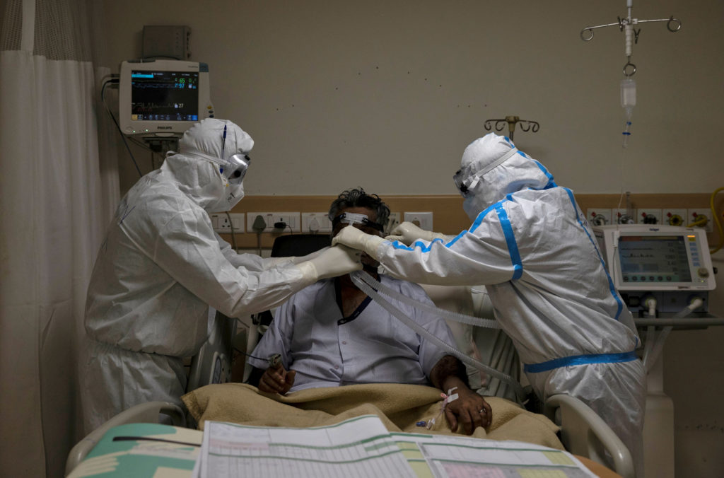 FILE PHOTO: Medical workers wearing personal protective equipment (PPE) take care of a patient suffering from the coronavi...