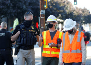 A Seattle Police officer talks to Seattle Department of Transportation employees as they back out after trying to enter and clear the CHOP area (Capitol Hill Occupied Protest), as people continue to occupy space and protest against racial inequality in the aftermath of the death in Minneapolis police custody of George Floyd, in Seattle, Washington, U.S. June 26, 2020. Photo by REUTERS/Lindsey Wasson