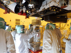 In this image taken on May 20, 2020 at the Kennedy Space Center, engineers and technicians insert 39 sample tubes into the belly of the rover. Each tube is sheathed in a gold-colored cylindrical enclosure to protect it from contamination. Perseverance rover will carry 43 sample tubes to the Red Planet's Jezero Crater. Photo from NASA/JPL-Caltech