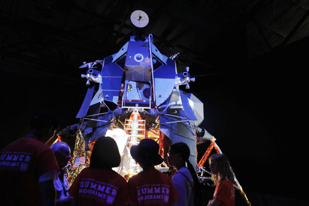 Summer camp attendees look at one of three remaining examples of the Lunar Modules used on the Apollo missions as it is di...