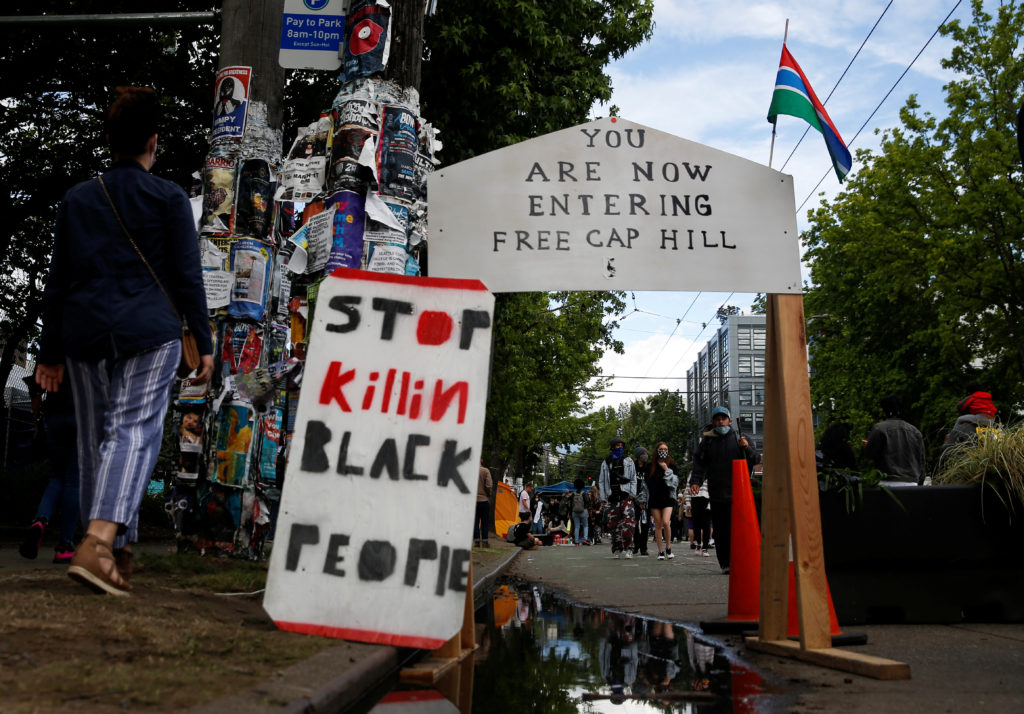 FILE PHOTO: People walk by signs at a barrier set up at the edge of the self-proclaimed CHAZ/CHOP zone around the Seattle ...