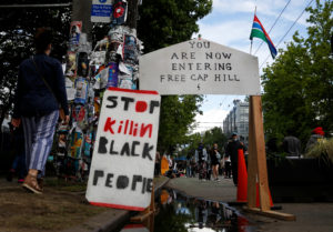 FILE PHOTO: People walk by signs at a barrier set up at the edge of the self-proclaimed CHAZ/CHOP zone around the Seattle Police Department's East Precinct as people call for the defunding of police and protest against racial inequality in the aftermath of the death in Minneapolis police custody of George Floyd, in Seattle, Washington, U.S. June 14, 2020.