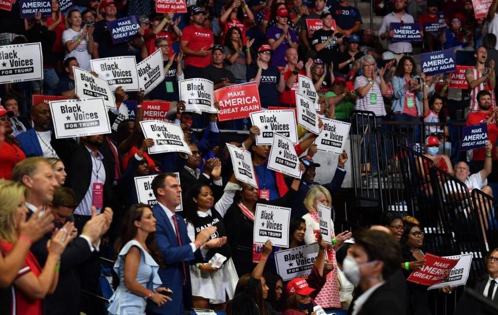 """Governor Kevin Stitt claps among """"Black Voices for Trump"""" supporters as US President Donald Trump speaks during a campaign rally at the BOK Center on June 20, 2020 in Tulsa, Oklahoma. - Hundreds of supporters lined up early for Donald Trump's first political rally in months, saying the risk of contracting COVID-19 in a big, packed arena would not keep them from hearing the president's campaign message. (Photo by Nicholas Kamm / AFP) (Photo by NICHOLAS KAMM/AFP via Getty Images)"""