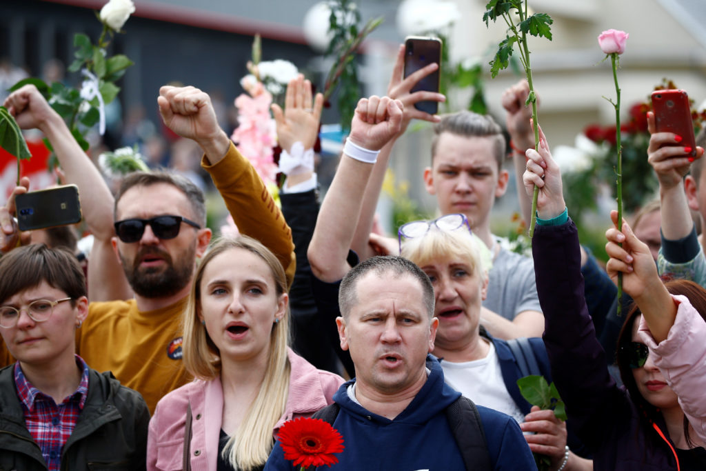 People hold flowers during a demonstration against violence following recent protests to reject the presidential election ...
