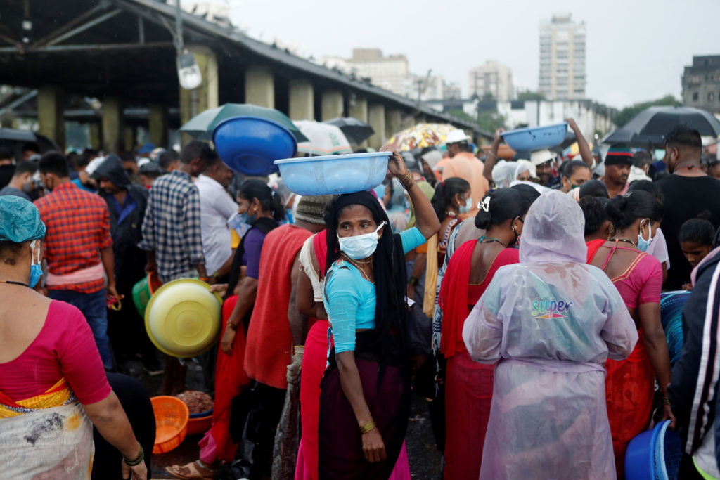 A fisherwoman wearing a protective mask is seen at a fish market am…