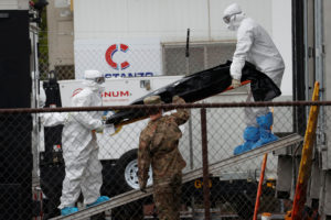 Workers wearing personal protective equipment (PPE) move the body of a deceased person from a refrigerated truck trailer set up at a temporary morgue outside University Hospital during the outbreak of the coronavirus disease (COVID-19) in Newark, New Jersey, U.S., May 6, 2020. Photo by REUTERS/Mike Segar