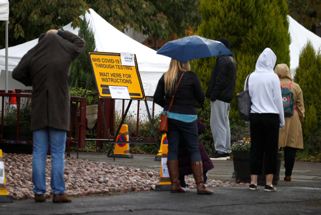 People stand in a queue to get tested for COVID-19 at a walk-through centre amid the coronavirus disease (COVID-19) outbre...
