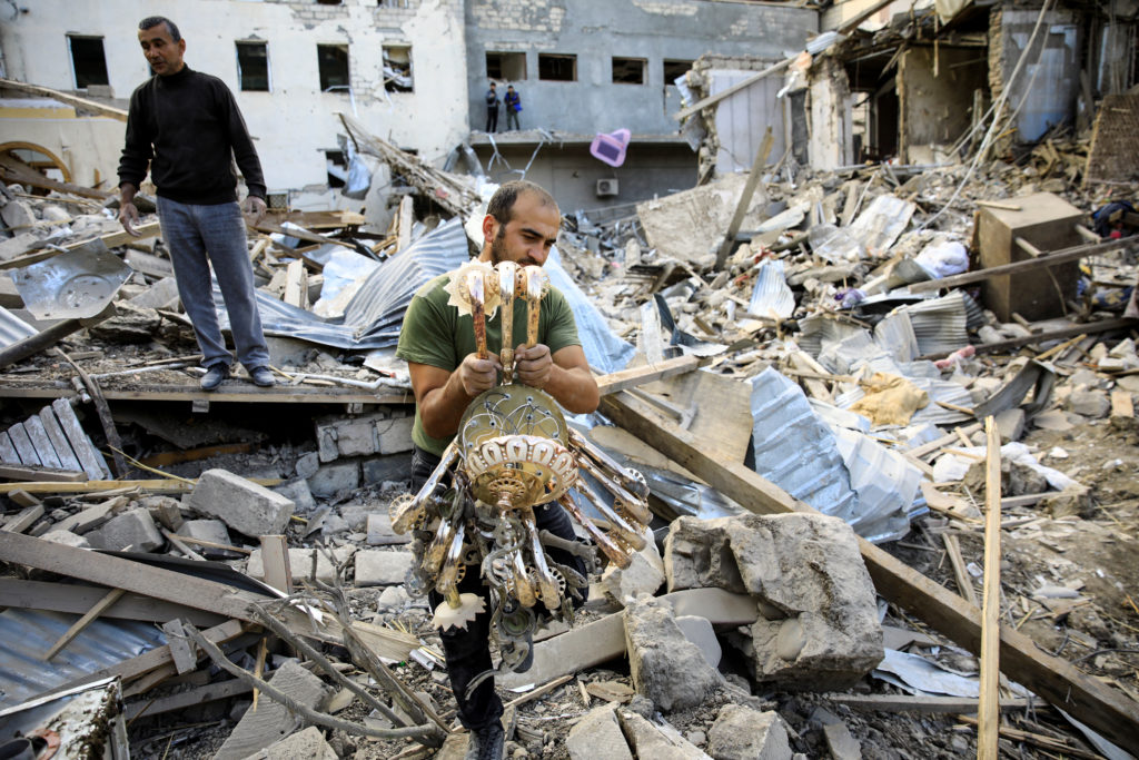 A man carries a chandelier away from the ruins at the blast site hit by a rocket during the fighting over the breakaway re...