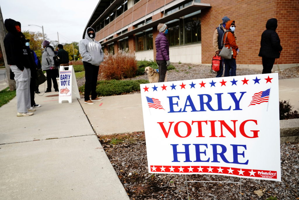 People queue to enter a polling site at the Milwaukee Public Librar…