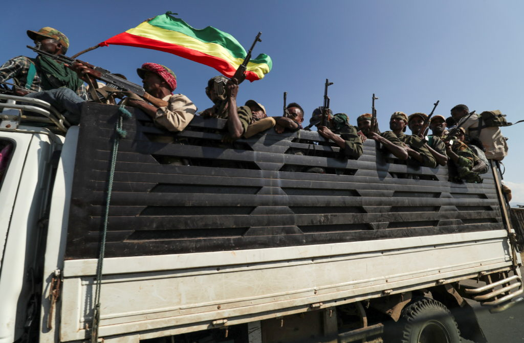 Members of Amhara region militias ride on their truck as they head to face the Tigray People's Liberation Front (TPLF), in...