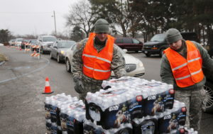 Michigan National Guard members help to distribute water to a line of residents in their cars in Flint, Michigan January 21, 2016. Photo by Rebecca Cook/Reuters
