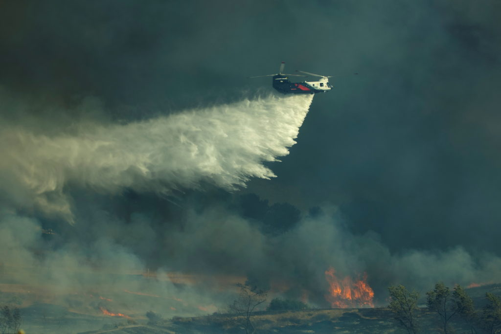 A helicopter drops water on a wind driven wildfire named the Bond Fire near Lake Irvine in Orange County, California, U.S., December 3, 2020. Photo by REUTERS/Mike Blake