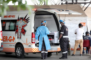 FILE PHOTO: Health workers chat near an ambulance at the parking lot of the Steve Biko Academic Hospital, amid a nationwide coronavirus disease (COVID-19) lockdown, in Pretoria, South Africa, January 11, 2021. REUTERS/Siphiwe Sibeko/File Photo
