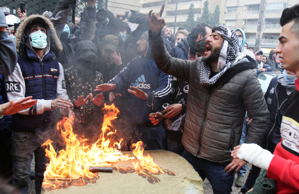A demonstrator gestures as others warm up near a fire during a prot…
