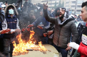 A demonstrator gestures as others warm up near a fire during a protest against the lockdown and worsening economic conditions amid the spread of the coronavirus disease (COVID-19), in Tripoli, Lebanon January 28, 2021. Photo by Reuters/Omar Ibrahim