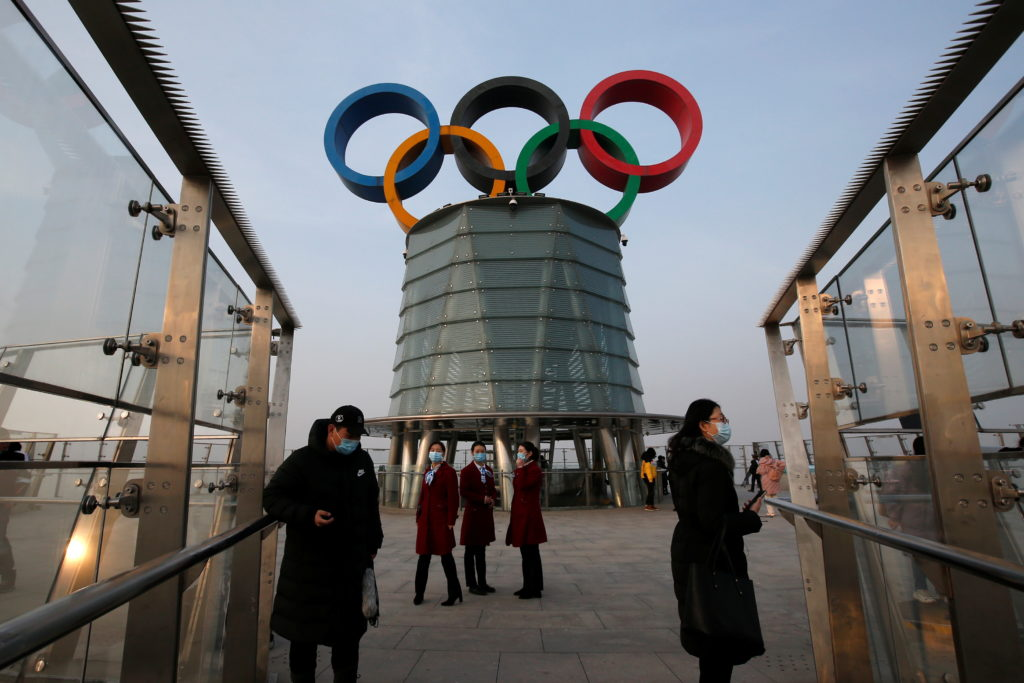 People wearing face masks following the coronavirus disease (COVDI-19) outbreak are seen near a giant Olympic symbols at the Olympic Tower, during an organised media tour to 2022 Winter Olympic Games venues in Beijing, China January 22, 2021. Photo by Reuters/Tingshu Wang