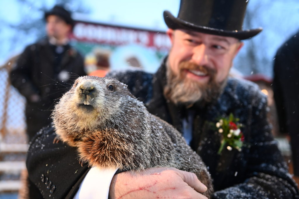 Punxsutawney Phil's handler A.J. Dereume holds the famous groundhog during a socially distanced and remote event due to the coronavirus disease (COVID-19) on the 135th Groundhog Day at Gobblers Knob in Punxsutawney, Pennsylvania, U.S., February 2, 2021. Photo by Reuters/Alan Freed