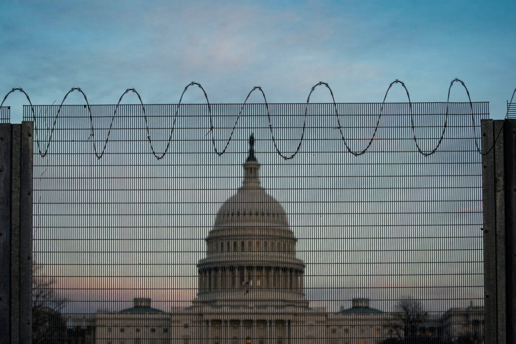 Barbed wire and protective fencing surrounds the U.S. Capitol, as the sun sets in Washington, U.S., February 21, 2021. Pho...