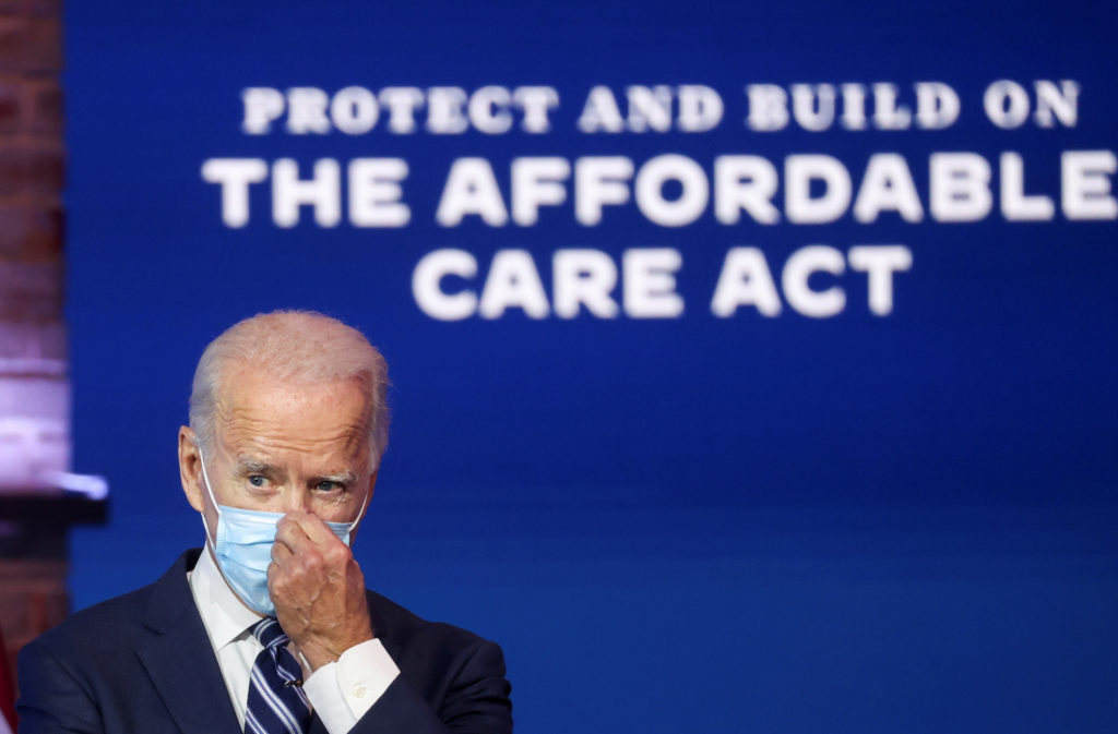 U.S. President-elect Joe Biden adjusts his face mask after during a news conference, where he discussed health care and th...