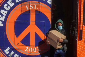 """A worker carries boxes of food distributed by the charity Lifecamp from their """"Peace Bus"""" amid the coronavirus disease (COVID-19) pandemic in the Brooklyn borough of New York City, New York, U.S., February 4, 2021. Picture taken February 4, 2021. Photo by Reuters/Carlo Allegri"""